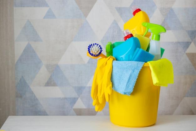 Produits de nettoyage et matériaux dans un seau jaune - seau de nettoyage isolé.