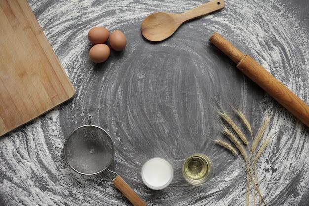 Produits et outils pour la cuisson du pain ou des gâteaux sur une table grise dans de la farine dispersée