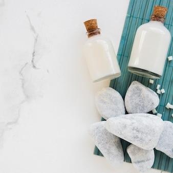 Produits pour le bain en gros plan dans des récipients en verre avec des roches