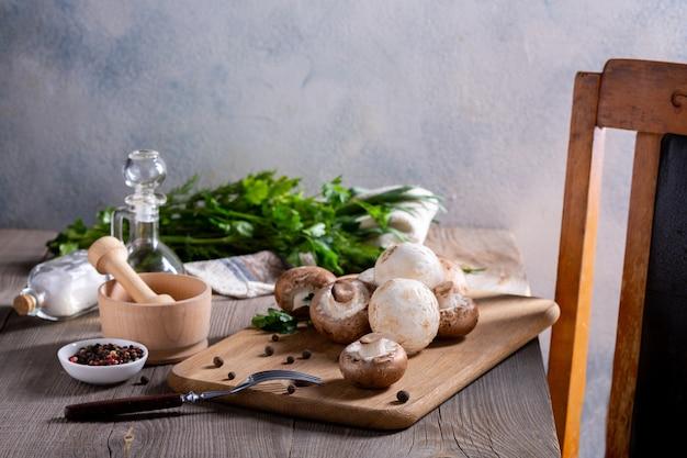 Produits pour la préparation de plats aux champignons. champignons, aneth, persil, oignons verts sur une table en bois. concept de cuisine