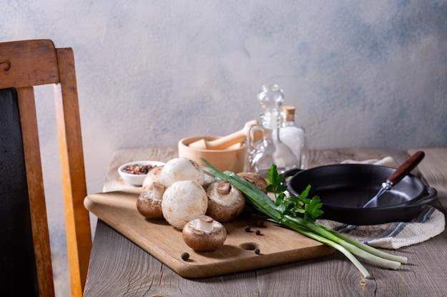 Produits pour la préparation de plats aux champignons. champignons, oignons verts sur une table en bois. concept de cuisine