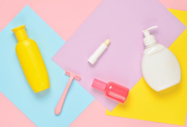 Produits pour le soin de la beauté féminine sur fond de papier coloré. bouteille de shampoing, savon, rasoir épilateur, flacon de parfum, rouge à lèvres, vernis à ongles. vue de dessus