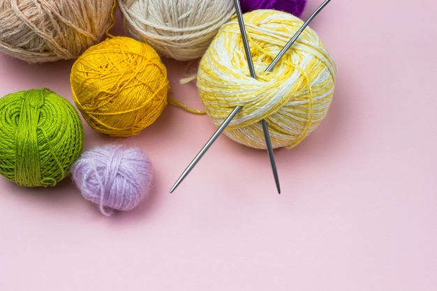 Produits pour travaux d'aiguille, tricot. boules de fil jaune, vert, violet, aiguilles à tricoter sur fond rose. espace pour le texte.