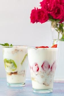 Produits sains pour le petit déjeuner, granola et baies fraîches sur une table blanche