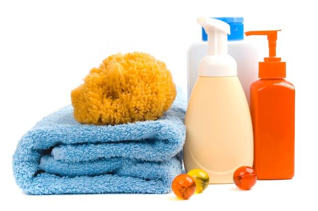Produits de soin du corps et serviette sur fond blanc