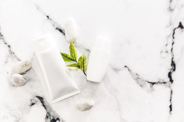 Produits de soin de peau de bouteille cosmétiques avec des pierres de spa et des feuilles sur fond de marbre blanc.