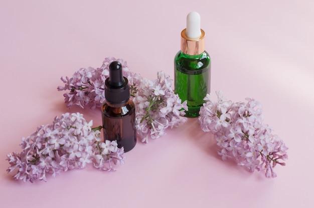 Produits de soin de la peau - huile essentielle et sérum - sertis de lilas frais, gros plan, lilas en arrière-plan. concept de soins de la peau et de beauté.