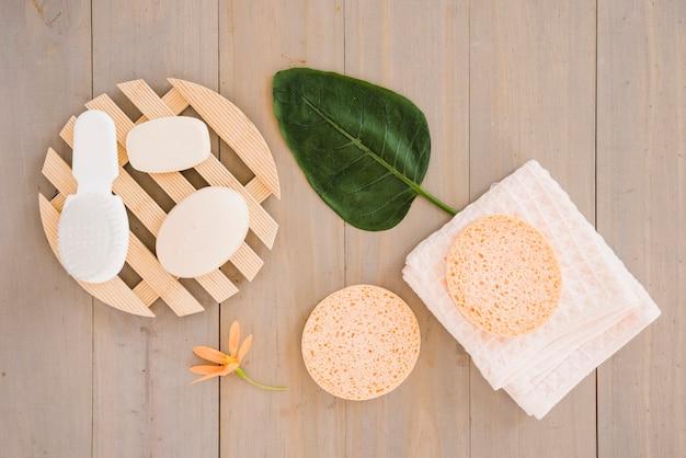 Produits de soin de la peau sur une serviette décorée de fleurs et de feuilles