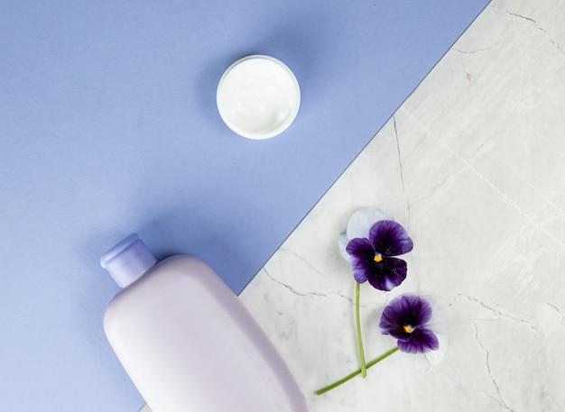 Produits de soin pour le corps et fleurs sur fond bleu