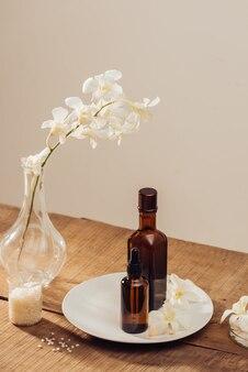 Produits de soins corporels, huiles essentielles dans des bouteilles brunes, sel de mer, ingrédients pour gommage corporel