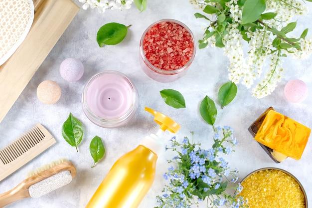 Produits de soins corporels naturels et accessoires disposés avec des fleurs et des feuilles