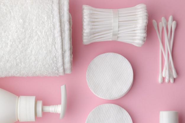 Produits de soins du corps et de la peau dans un emballage blanc sur une table rose