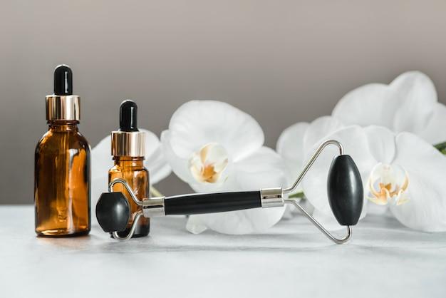 Produits de soins du corps et de la peau, flacons compte-gouttes et rouleau de massage guasha en pierre d'obsidienne dans la salle de bain avec fleurs d'orchidées, maquette de marque de produit cosmétique spa