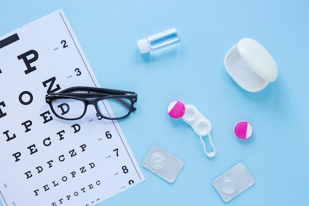 Produits de soins oculaires plats sur fond bleu
