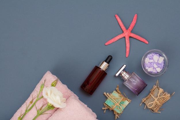 Produits de spa pour les soins du visage et du corps. sel de mer naturel, savon fait maison, bouteille d'huile, parfum et serviettes roses avec des fleurs sur fond gris. concept de spa et de soins du corps. vue de dessus.