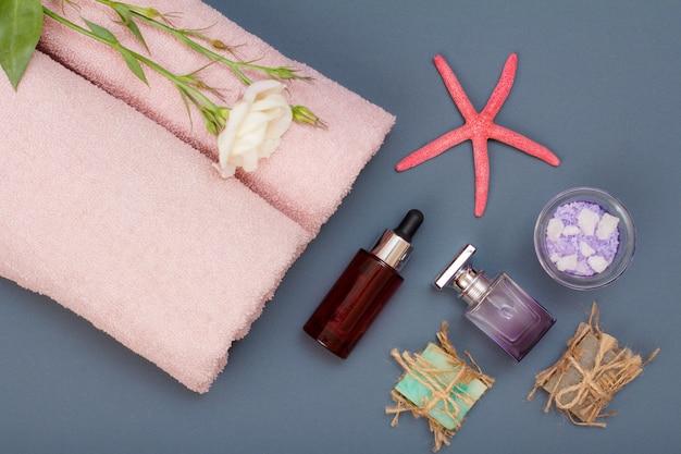 Produits de spa pour les soins du visage et du corps. sel de mer naturel, savon fait maison, huile aromatique, parfum et serviettes roses avec fleur et étoile de mer sur fond gris. concept de spa et de soins du corps. vue de dessus.