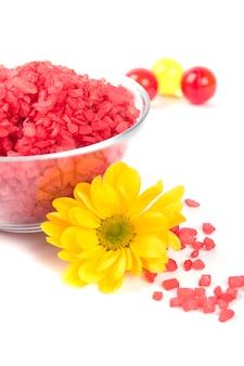 Produits de spa: sel de bain, boules d'huile dans un bol et fleur jaune