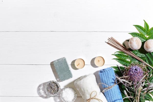 Produits de spa sels de bain fleurs sèches lavande savon bougies et serviette à plat sur backgro en bois blanc