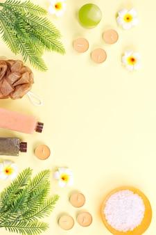 Produits de spa et de soins du corps à plat. gommage corporel, sel de bain, lotion hydratante, bougies et feuilles sur woodentable