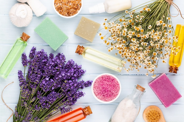 Produits de toilettage et bouquet de lavande fraîche sur fond de table en bois blanc.