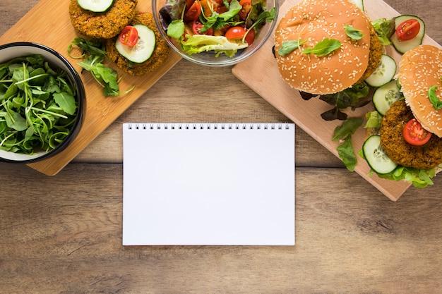 Produits végétaliens à côté d'un cahier vide sur une table en bois