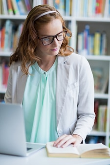 Prof, regarder, livre, quoique, utilisation, ordinateur portable, bibliothèque