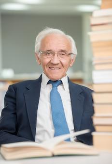 Professeur âgé avec des livres à l'intérieur de la salle de bibliothèque du collège
