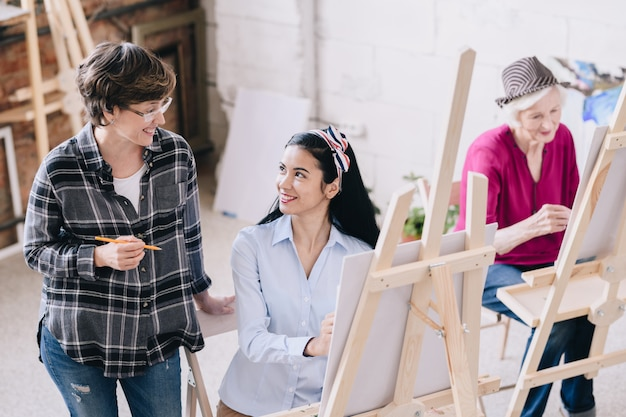 Professeur d'art féminin souriant à l'étudiant