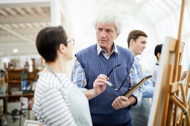 Professeur d'art senior parlant à un étudiant