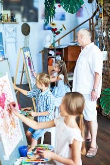 Professeur d'art senior travaillant avec des enfants