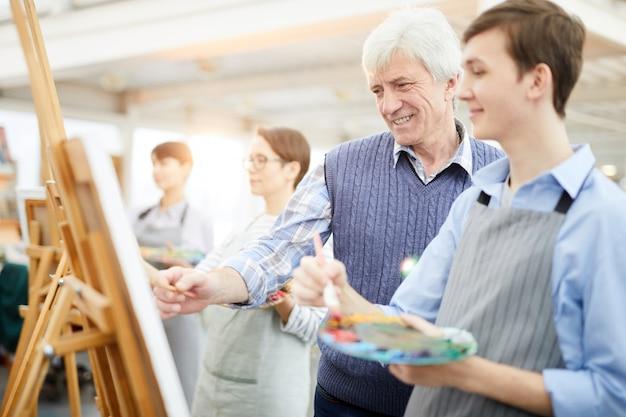 Professeur d'art souriant aidant les élèves