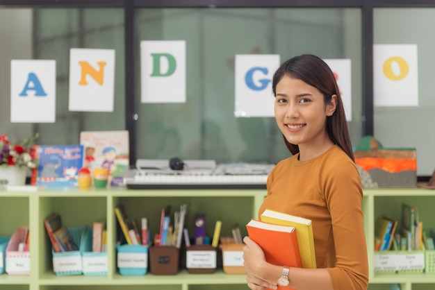 Un professeur assez asiatique souriant à la caméra au dos de la salle de classe à l'école élémentaire. photos de style effet effet vintage.