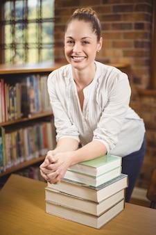 Professeur blonde s'appuyant sur une pile de livres dans la bibliothèque