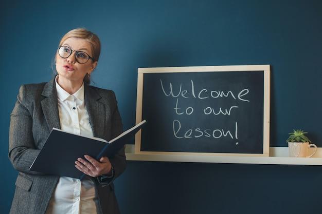 Professeur blonde senior enseigne devant la classe près du tableau tenant un livre