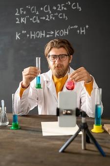 Professeur de chimie montrant une réaction chimique lors du mélange de deux substances liquides lors de travaux de laboratoire en ligne devant l'appareil photo du smartphone