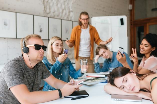 Professeur en colère debout près du tableau et hurlant sur les élèves parce qu'ils ne l'écoutent pas