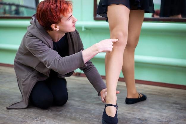 Le professeur de danse montre à son élève comment mettre les jambes correctement
