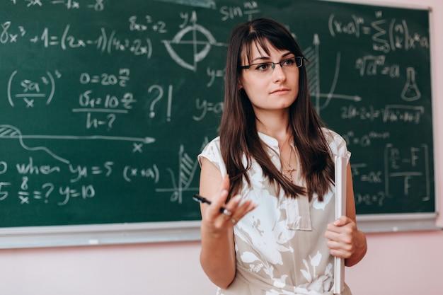 Le professeur debout à côté d'un tableau et explique une leçon.
