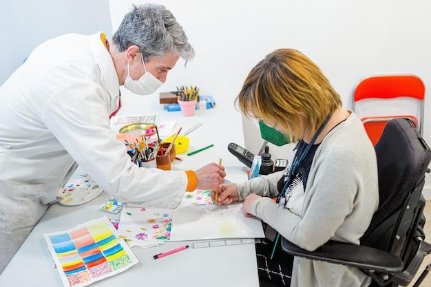 Professeur de dessin enseignant à un élève handicapé en fauteuil roulant