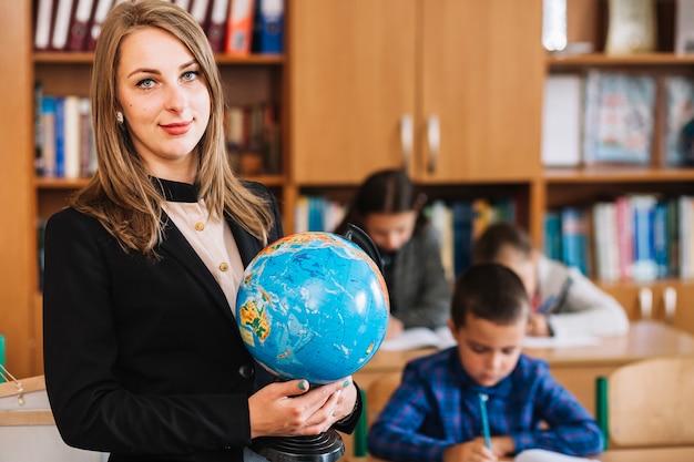 Professeur d'école avec globe sur fond d'élèves