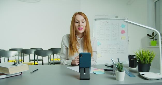 Professeur de femme assis à table et donnant des conférences en ligne en classe.