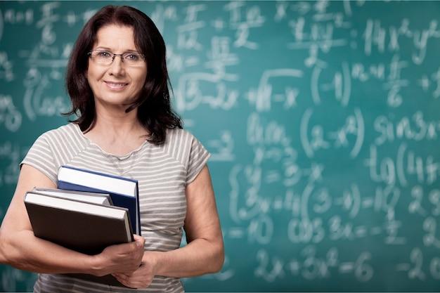 Professeur de femme mûre avec des livres sur le fond