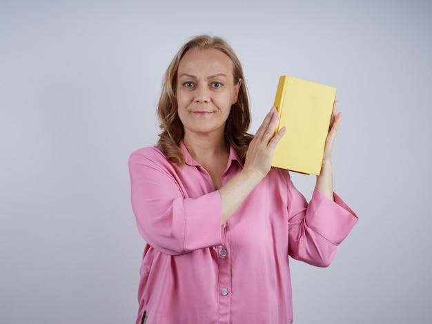 Professeur de femme mûre souriante, bibliothécaire en chemise rose, tenant un livre jaune, regardant. notion d'éducation.