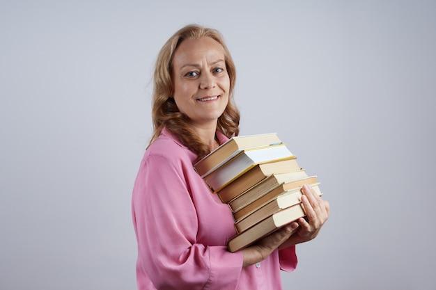 Professeur de femme mûre souriante, bibliothécaire en chemise rose, tenant une pile de livres, à la recherche. notion d'apprentissage.