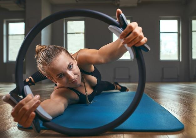 Professeur de gymnastique élégant, les mains inversées soutiennent le corps sur le sol et les jambes sur l'anneau de pilates avec corps extensible développent la douceur dans le studio de surface de mur gris