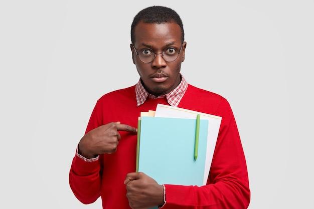 Un professeur indigné se montre du doigt, pose des questions sur ses fonctions, porte un manuel, porte un pull rouge décontracté, va organiser un séminaire pour les scientifiques isolé sur un mur blanc
