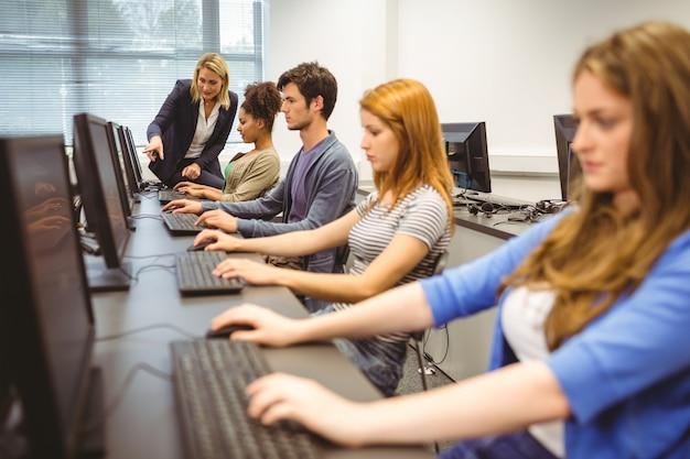 Professeur d'informatique aidant une jolie étudiante dans sa classe