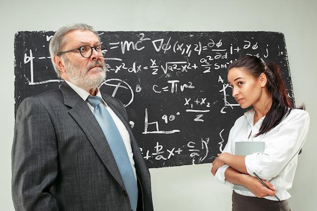 Professeur masculin et jeune femme contre le tableau noir en classe