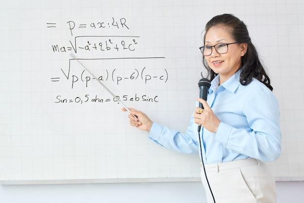 Professeur de mathématiques parlant au microphone en pointant sur l'équation sur le tableau blanc et expliquant un nouveau sujet aux étudiants