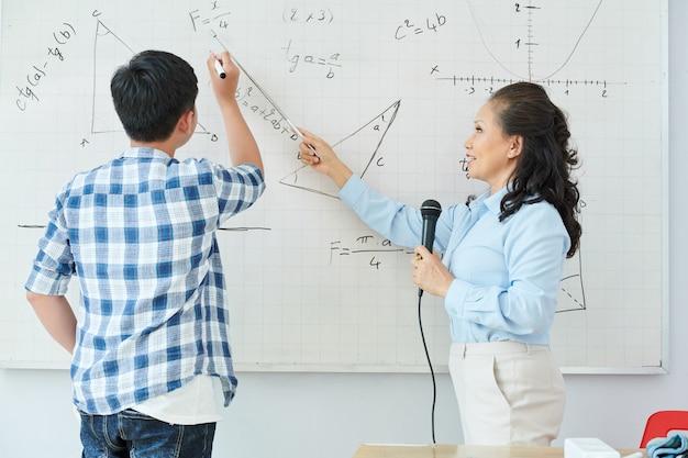 Professeur de mathématiques vietnamien mature parlant au microphone et pointant sur la formule sur le tableau blanc lors de la résolution de l'équation des élèves